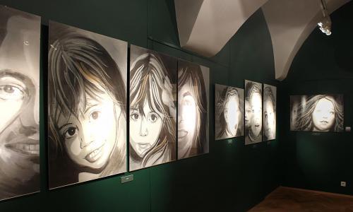 Jedna ze ścian pomieszczenia ekspozycyjnego z zawieszonymi portretami
