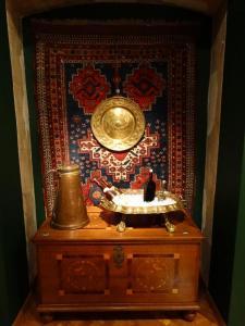 Na skrzyni stoją: wanna do chłodzenia wina i konew, w tle dywan, na którym zawieszono mosiężną misę