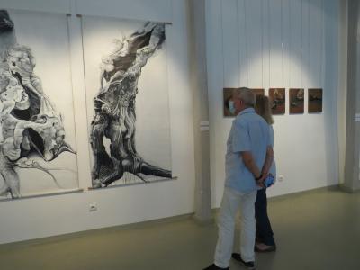 Goście zaproszeni na wernisaż wystawy, podziwiają prace artystki.