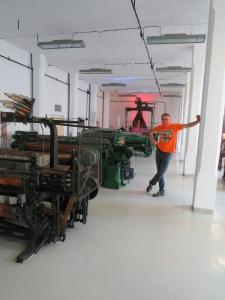 Jakub Krajewski obok maszyn włókienniczych