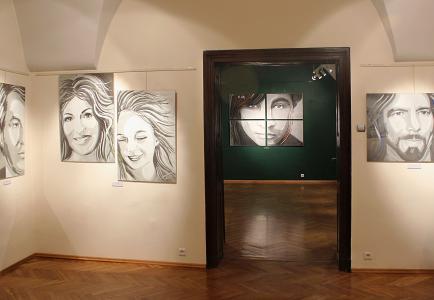 Kilka portretów wiszących na ścianie, w głębi kolejna sala ekspozycyjna