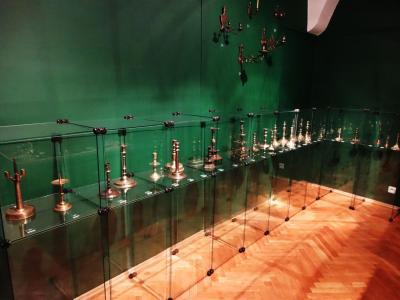 Ekspozycja 25 świeczników z brązu i mosiądzu. Powyżej gablot, na ścianie 5 kinkietów z brązu.