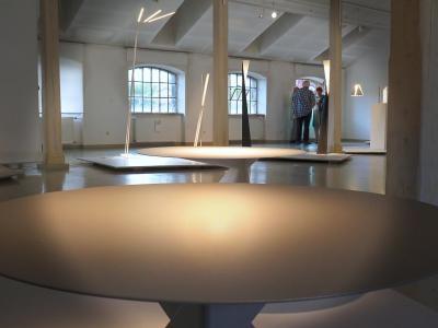 Dwa okrągłe stoliki. W tle kilka lamp.