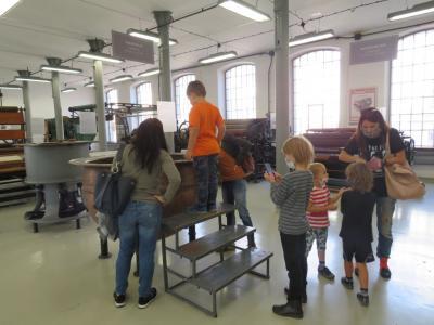 Kilka osób zwiedza ekspozycję urządzeń włókienniczych