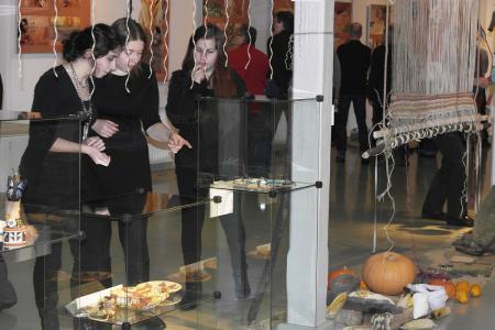 Trzy młode osoby dyskutują na temat wystawy