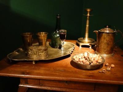 Stół dębowy, intarsjowany, na którym ustawiona została martwa natura: dzban, misa, lampa, kubki.