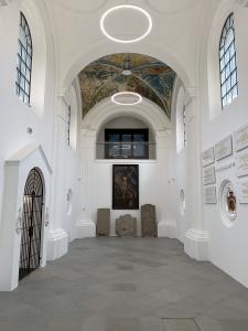 Wnętrze kaplicy, widok na emporę. Po lewej wejście, po prawej tablice pamiątkowe.