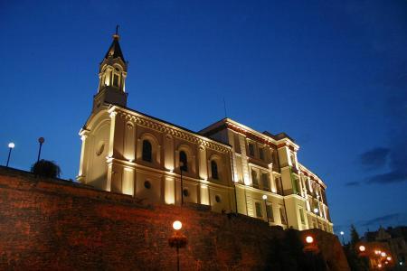 Nocny widok na kaplicę wznoszącą się ponad murem zamkowym