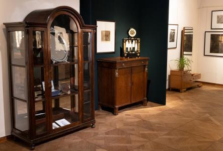 Fragment ekspozycji: biedermeierowska przeszklona witryna z lustrem w zaplecku, XIX-wieczna komoda i zegar zdobiony lustrem oraz toaletka z lustrem z lat 30. XX wieku, na ścianach grafiki.