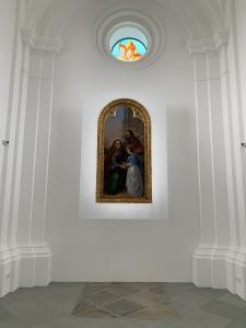 Obraz wiszący na ścienie, powyżej okno z witrażem.