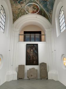 Widok na emporę pod którą znajduje się obraz z ukrzyżowanym Chrystusem.